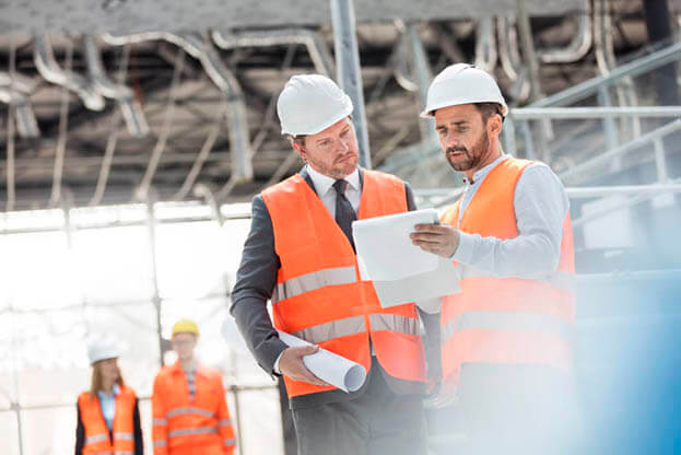 Engineers with blueprints and clipboard discussing paperwork at construction site