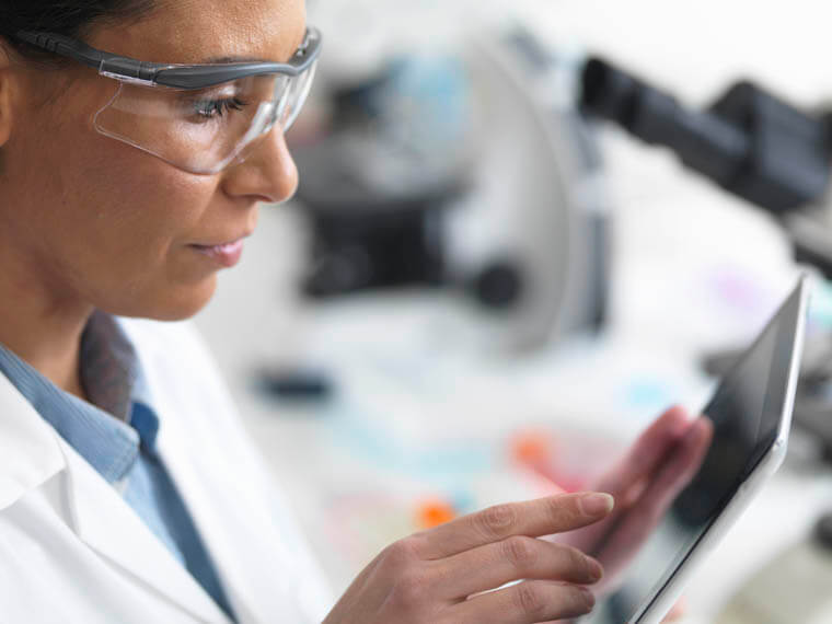 Scientist viewing test results on a digital tablet in lab